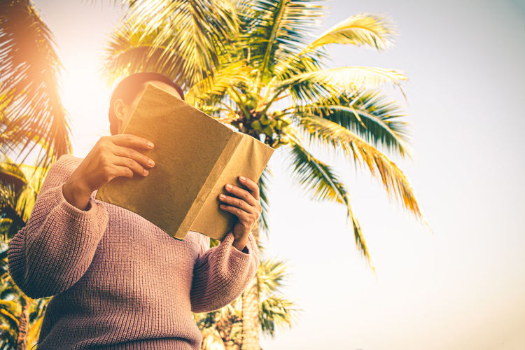 Midsection of man holding book against sky