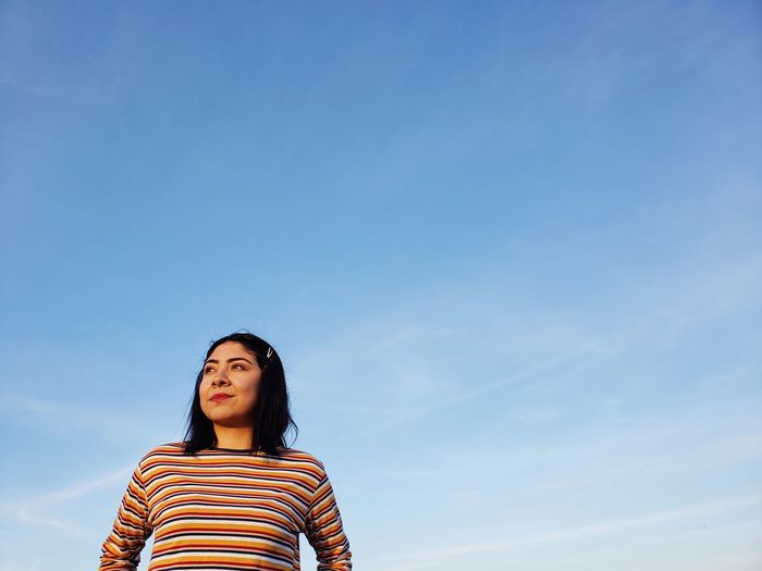 Portrait of young woman standing against blue sky