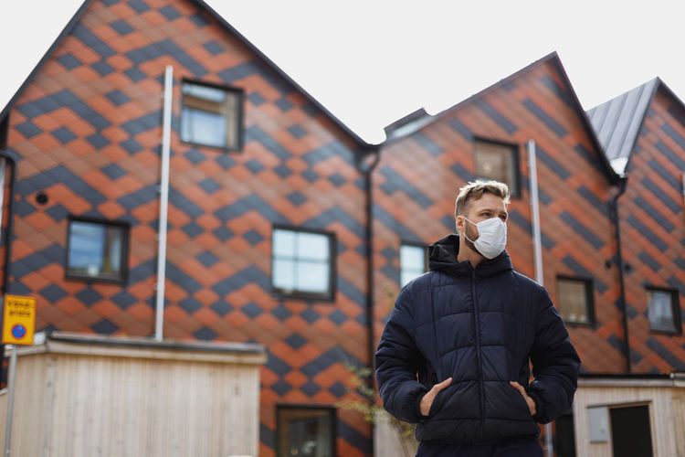 Portrait of man standing against building