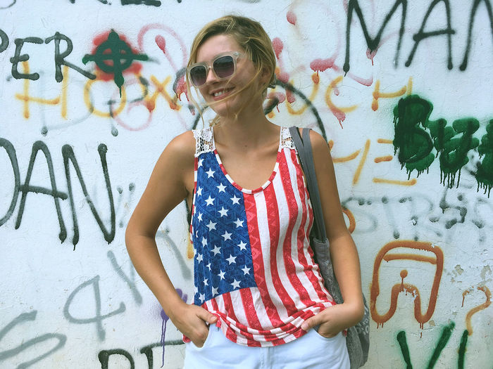 Young Woman Wearing American Flag Tank Top While Standing Against Graffiti Wall