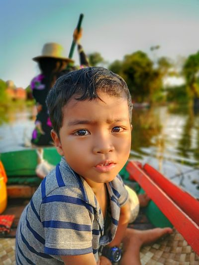 Portrait of cute boy sitting in boat with woman rowing in background