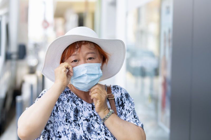 Portrait of mature woman wearing flu mask and hat standing outdoors