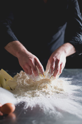 CROPPED VIEW OF CHEF'S HANDS MAKING PASTRY