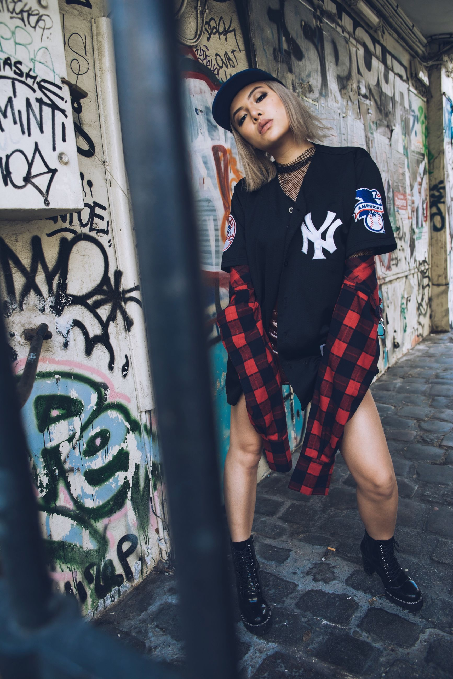 real people, graffiti, full length, one person, lifestyles, young women, young adult, front view, standing, casual clothing, leisure activity, built structure, architecture, looking at camera, fashion, outdoors, day, beautiful woman, happiness, portrait, building exterior, smiling