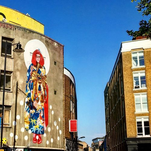 Low angle view of graffiti on building against clear blue sky