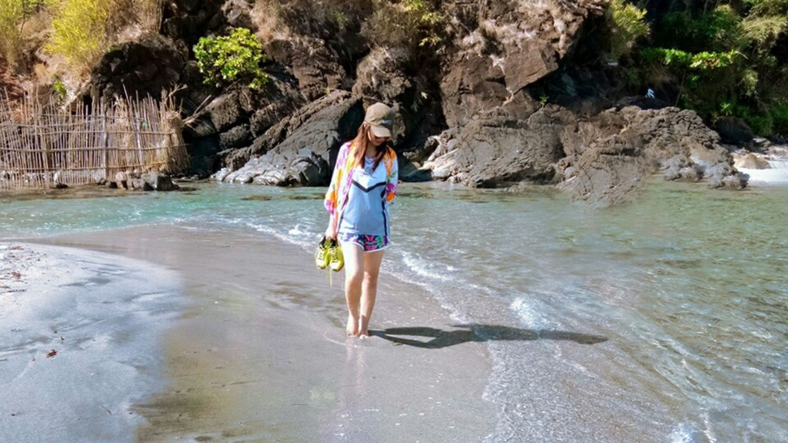 looking at camera, rock - object, portrait, full length, vacations, smiling, one person, front view, only women, one woman only, outdoors, long hair, water, day, happiness, young adult, beach, adults only, beautiful woman, beauty, adult, one young woman only, sea, people, nature, ankle deep in water, young women