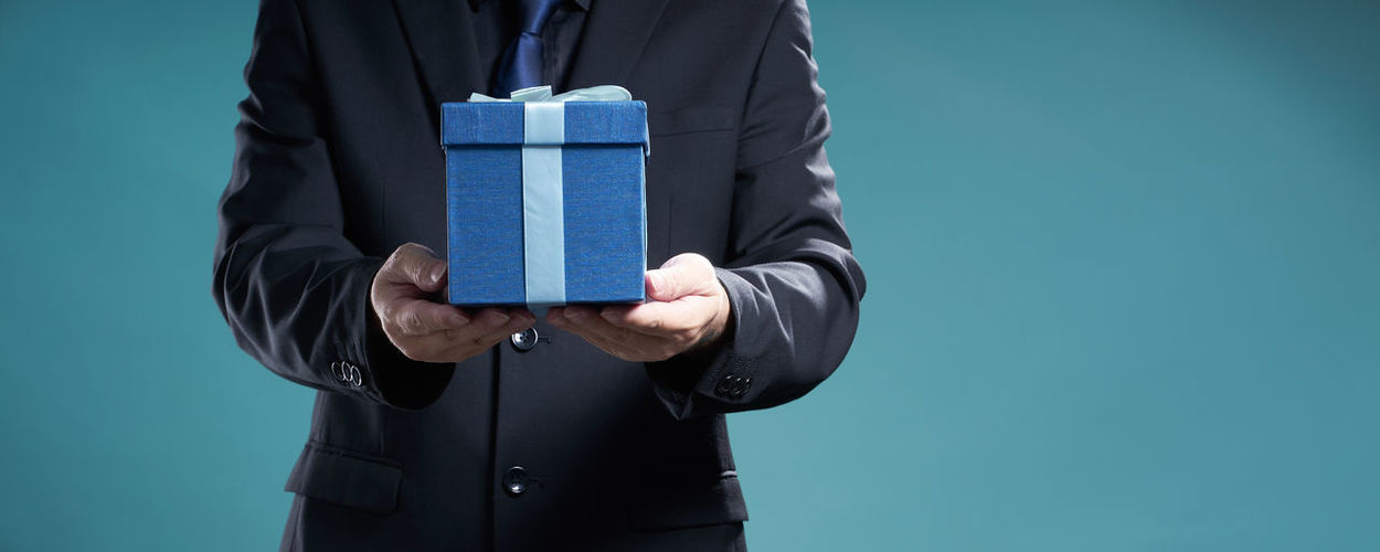Mid Section Of Businessman Holding Gift Box Over Blue Background