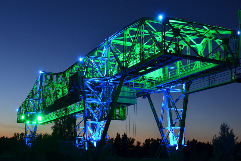 Low angle view of illuminated industrial metallic structure