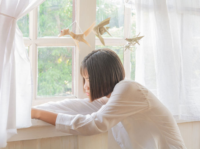 Side view of teenage girl looking through window at home