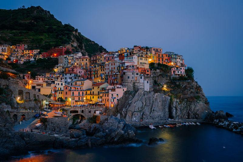 Illuminated buildings by sea against clear sky