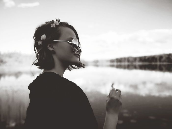 Side view of young woman standing by lake against sky