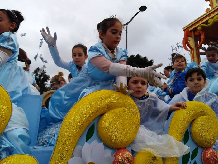 kids having fun throwing away candies during the Three Kings Parade Yellow Blue Three Kings Parade Festival Kids Girls Outfit Traditional Party Child Childhood Togetherness Boys Portrait Girls Fun Happiness Smiling