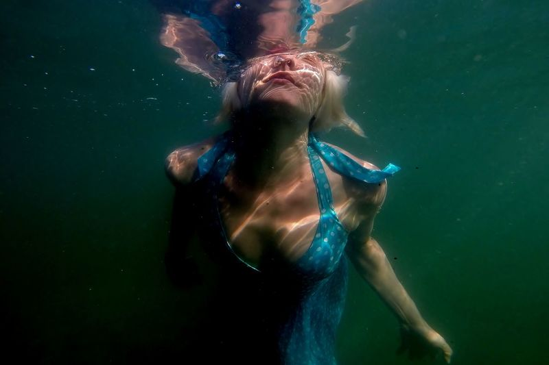 Close-Up Of Woman Swimming In Sea