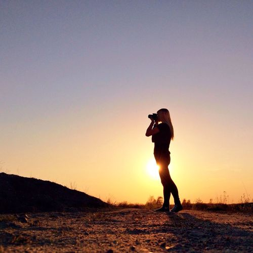 Silhouette woman photographing landscape at sunset