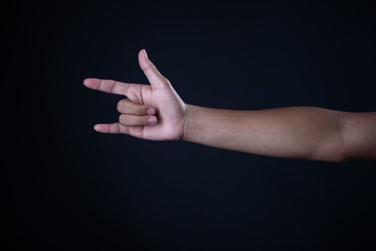 Close-up of hand pointing over black background
