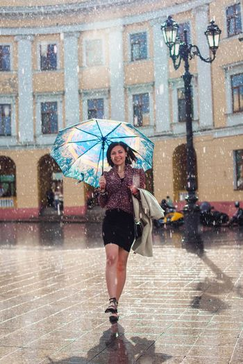 Full length portrait of cheerful woman walking with umbrella at fountain