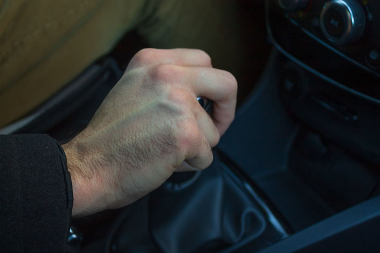 Man hand on gear lever in car