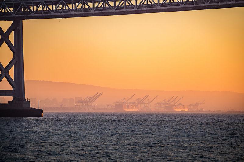 Cranes at harbor against sky