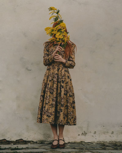 woman standing against wall with mimosa flowers