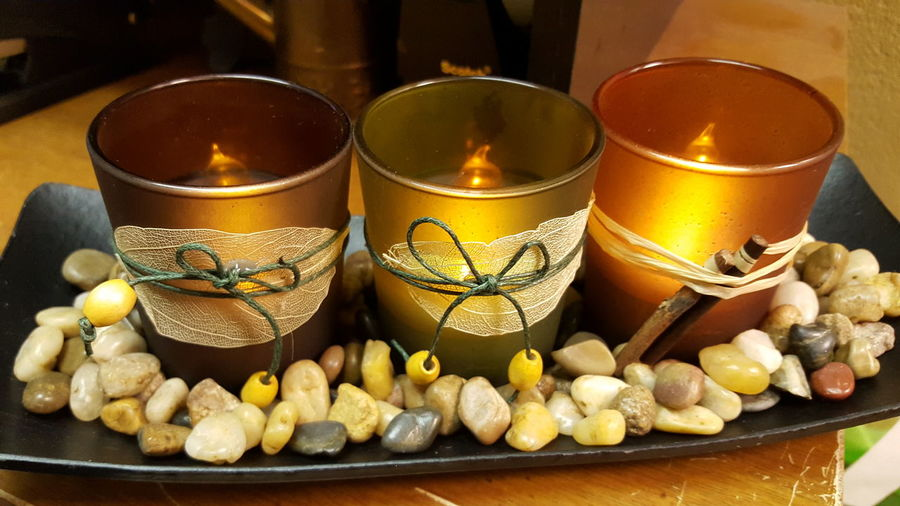 High Angle View Of Candles With Pebbles Decoration In Tray On Table