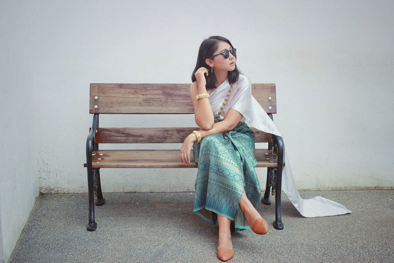 Full length of young woman sitting on bench