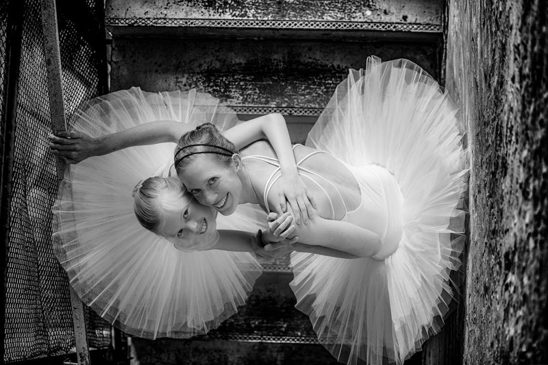 Directly above portrait of smiling woman and girl wearing tutu on steps