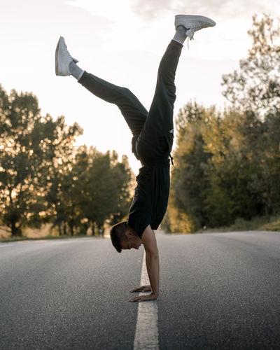 Full length of man skateboarding on road in city