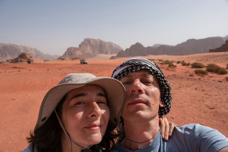 Portrait of couple at desert against clear sky