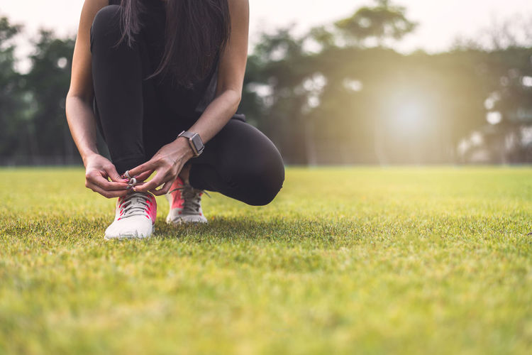 Low section of woman tying shoelace on grassy land