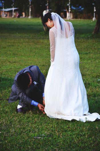 Groom adjusting bride sandal on field
