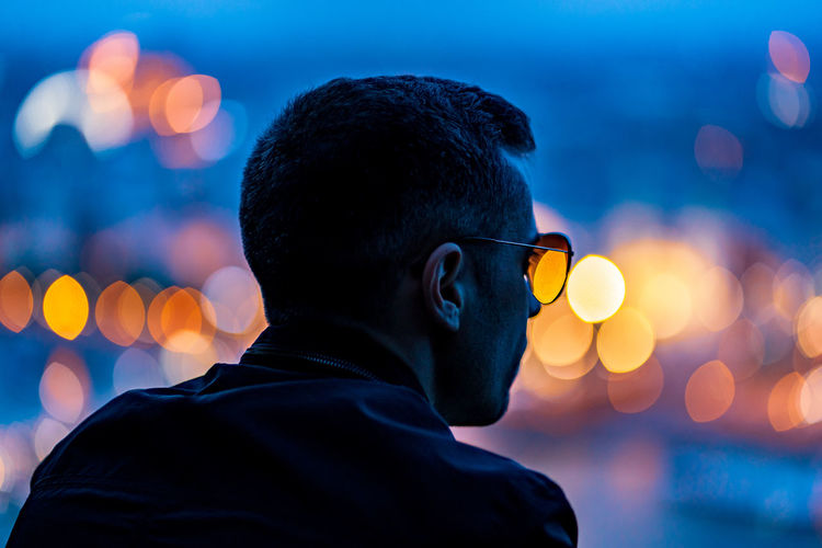 Rear view of man in sunglasses outdoors at dusk