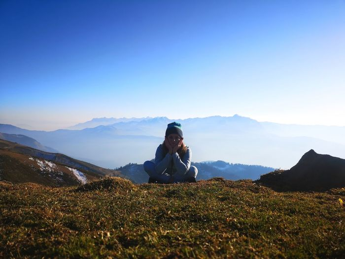 Sitting on mountain against sky