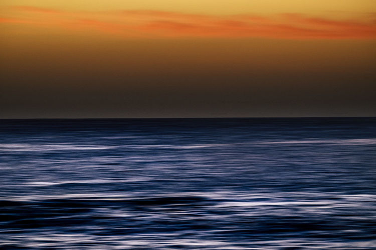 Sunset or sunrise moment over the ocean with sun touching the horizon line on the water - romantic and touristic concept for travel vacation background coloured Clean Dawn Island Horizontal Horizon Over Water Nature Atlantic Ocean Red Romance Suggestive Season  Sea Sky Time Tourist Turism Freedom Movement Motion Colored Background Wallpaper Seascape Tenerife Canary Islands Water Sunset Horizon Scenics - Nature Beauty In Nature Tranquility Tranquil Scene Wave Idyllic Cloud - Sky No People Dusk Environment Sun Abstract Outdoors