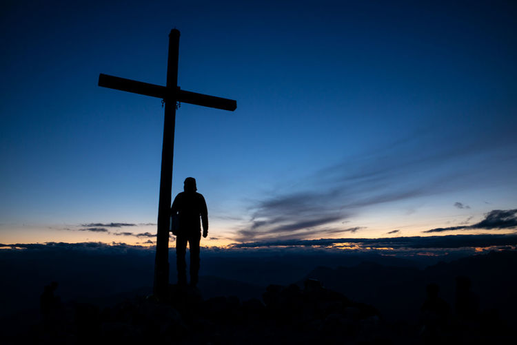 Silhouette men standing by cross against sky during sunset