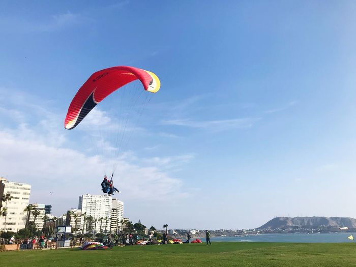 Real People Leisure Activity Parachute Lifestyles Day Sky Architecture Flying Adventure Outdoors Extreme Sports Sport Large Group Of People Paragliding Activity Mid-air Built Structure Men Vacations Grass EyeEmNewHere Perspectives On Nature