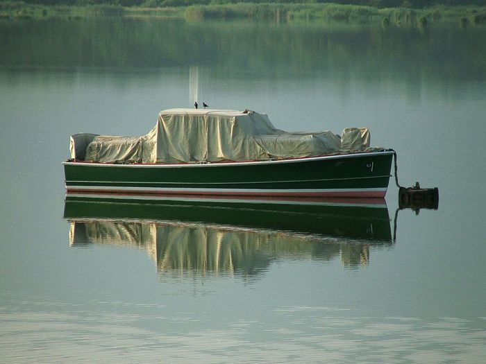 Full length of nautical vessel in reflection lake