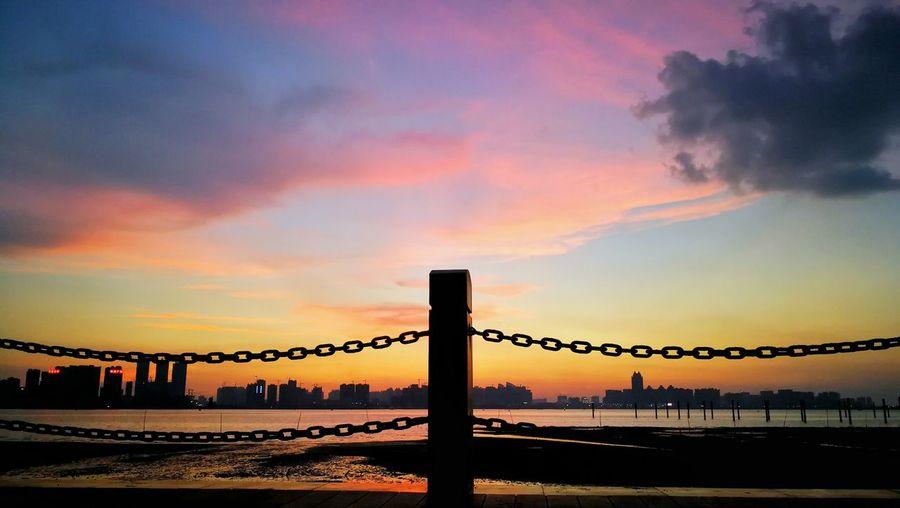 Silhouette bridge over sea against dramatic sky during sunset