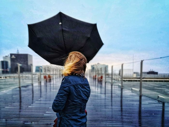 Rear view of woman holding umbrella while standing by railing against sky