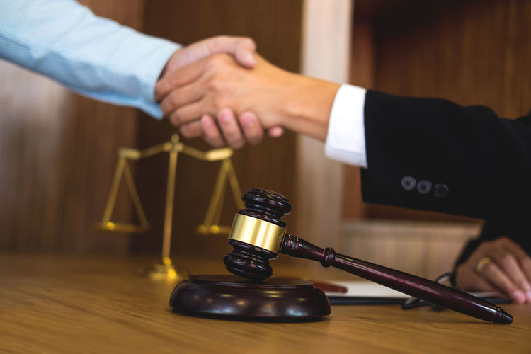 Cropped hands of lawyer giving handshake to client at desk in office