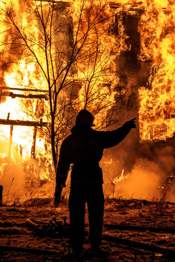 Firefighter standing by burning fire at night