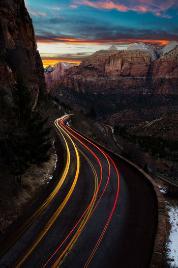 Light trails on road by rock formation against sky