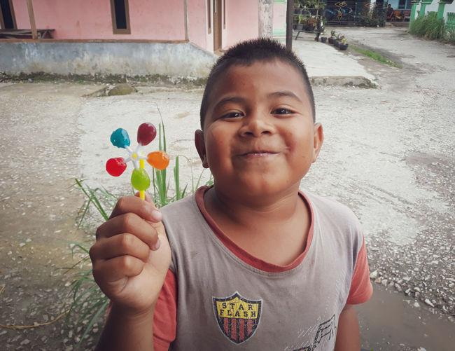 Portrait of smiling boy holding camera