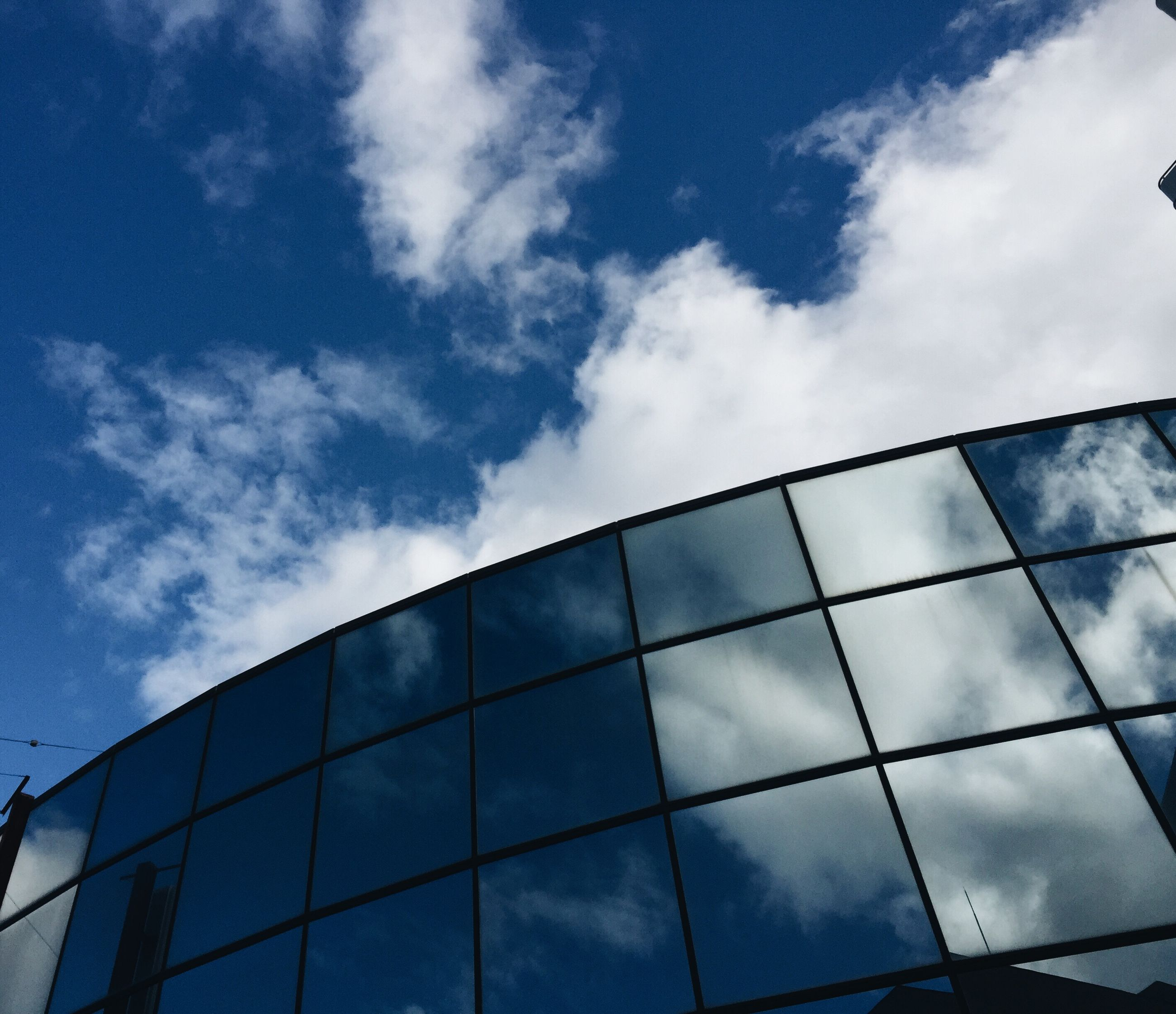 architecture, sky, low angle view, built structure, building exterior, cloud - sky, modern, cloud, blue, office building, glass - material, reflection, city, cloudy, building, day, pattern, no people, outdoors, window