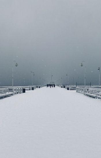 Snow covered street against sky