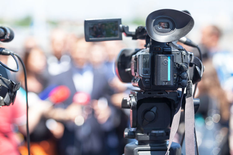 Close-Up Of Television Camera Filming Interview In City