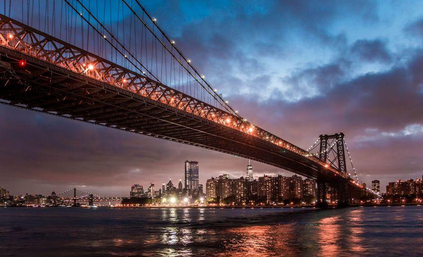 Illuminated suspension bridge over river against cloudy sky