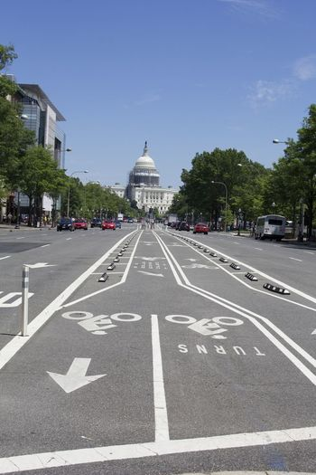 Road Leading Towards Capitol Building Against Sky On Sunny Day