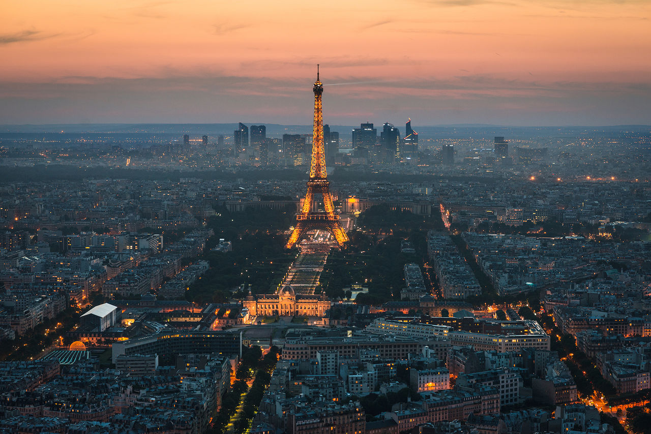 High Angle View Of Cityscape With Illuminated Eiffel Tower During Sunset