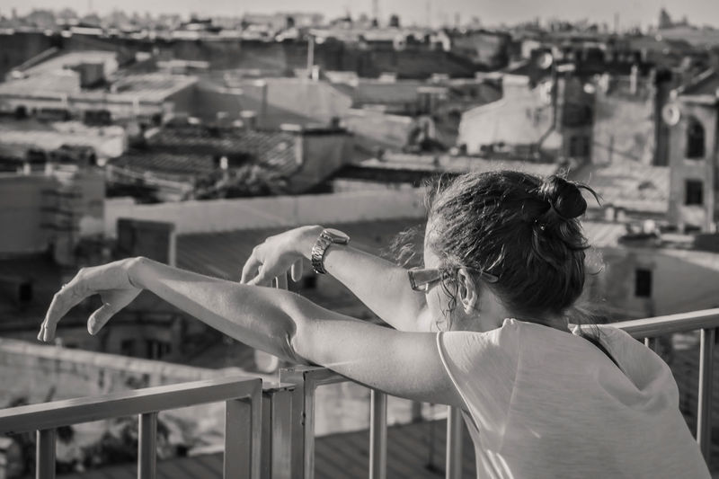 Rear view of woman standing by railing in city