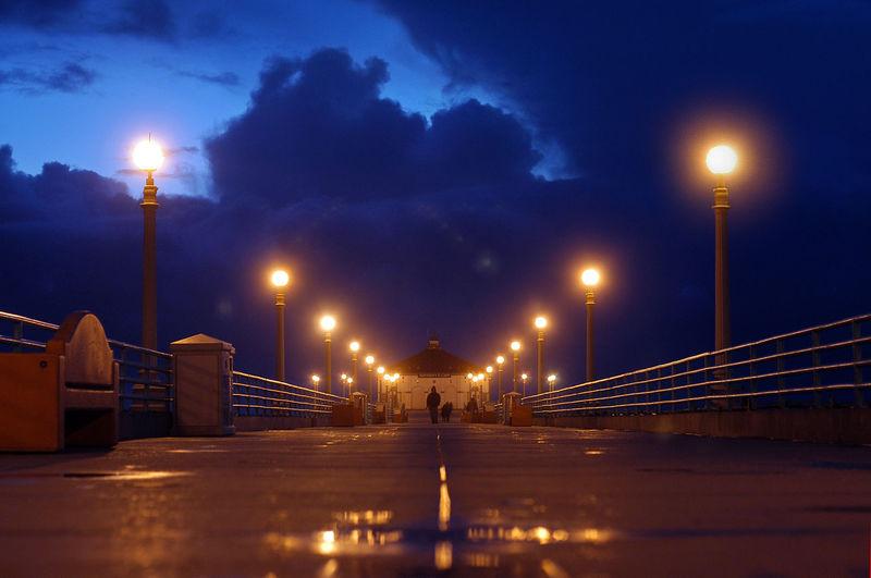 View of illuminated pier at night